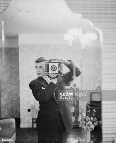 A Fox Photos staff photographer captures his own image in a mirror circa 1948
