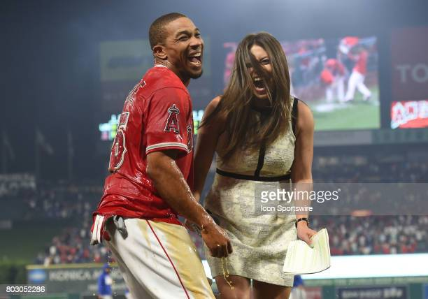 Fox Sports announcer Alex Curry and Los Angeles Angels of Anaheim Outfield Ben Revere share a laugh after Curry was doused with Powerade to celebrate...
