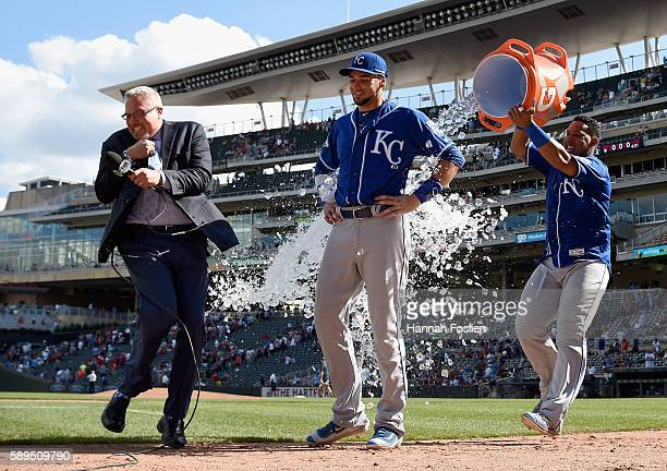 Fox Sports announcer Joel Goldberg gets out of the way as Salvador Perez of the Kansas City Royals pours water on teammate Paulo Orlando to celebrate...