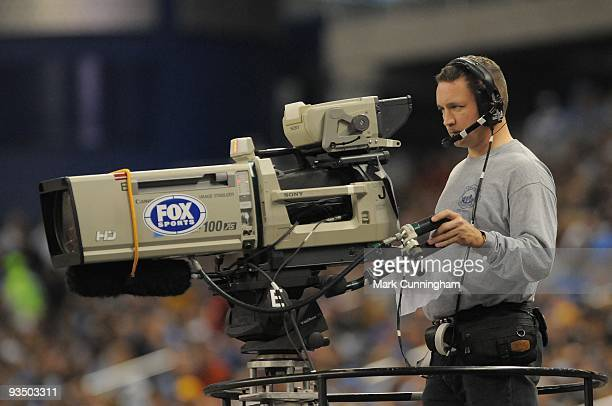 Fox Sports cameraman runs a TV camera during the game between the Detroit Lions and the Green Bay Packers at Ford Field on November 26 2009 in...