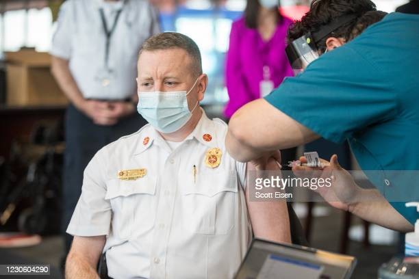 Foxborough Fire Chief Michael Kelleher receives his COVID-19 vaccine at Gillette Stadium on January 15, 2021 in Foxborough, Massachusetts. First...