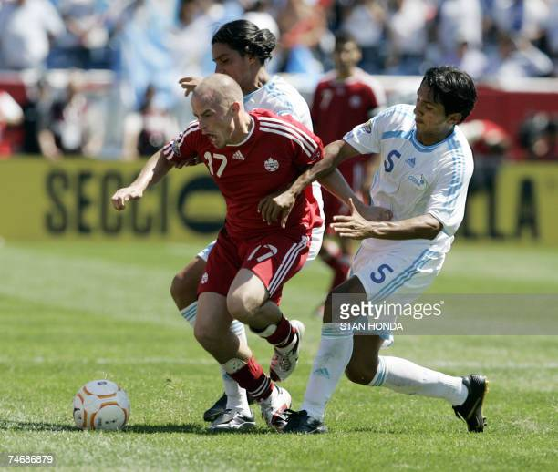 Foxborough, UNITED STATES: Iain Hume of Canada tries to hold off Gustavo Cabrera and Henry Medina of Guatemala during a quarterfinal game at the...