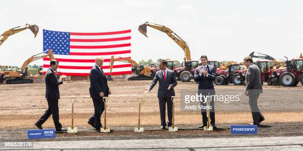 Foxconn CEO Terry Gou gestures to US President Donald Trump at the groundbreaking of the Foxconn Technology Group computer screen plant on June 28...