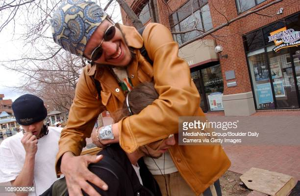 Foxfire, top, hugs his friend Puck as he stands on a bench on the Pearl Street Mall on a recent weekday .