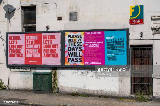 A Foxtons Group Plc real estate agents sold sign on a residential property next to billboards with messaging relating to the coronavirus pandemic in...