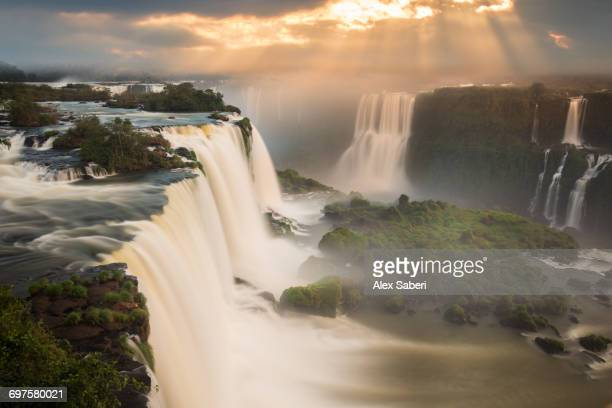 Iguazu falls waterfall at sunset.