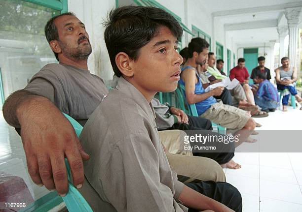 Fozi a 12yearold Iraqi refugee sits near his father Ammar at a refugee camp October 24 2001in Bogor West Java Indonesia Fozi's mother was killed...