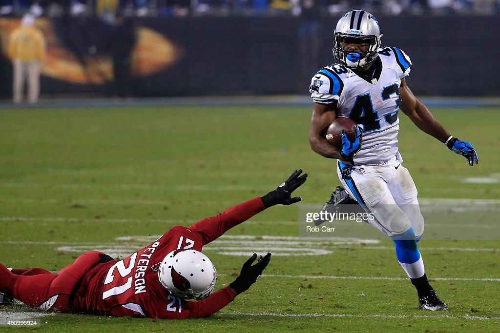 Fozzy Whittaker #43 of the Carolina Panthers avoids a tackle from Patrick Peterson #21 of the Arizona Cardinals during their NFC Wild Card Playoff game at Bank of America Stadium on January 3, 2015 in Charlotte, North Carolina. Whittaker took it to the endzone for a touchdown.