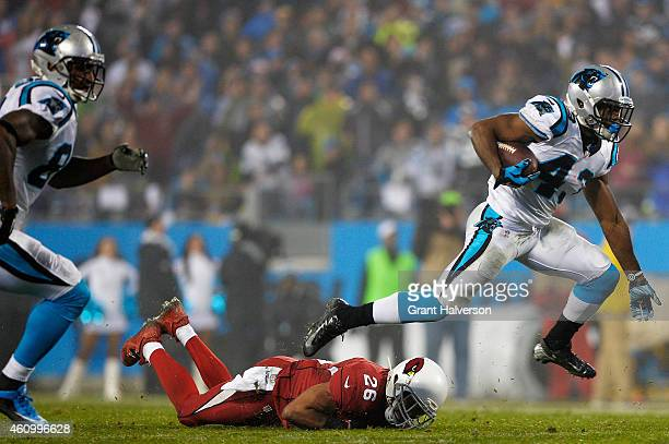 Fozzy Whittaker of the Carolina Panthers tries to avoid the tackle of Rashad Johnson of the Arizona Cardinals during their NFC Wild Card Playoff game...