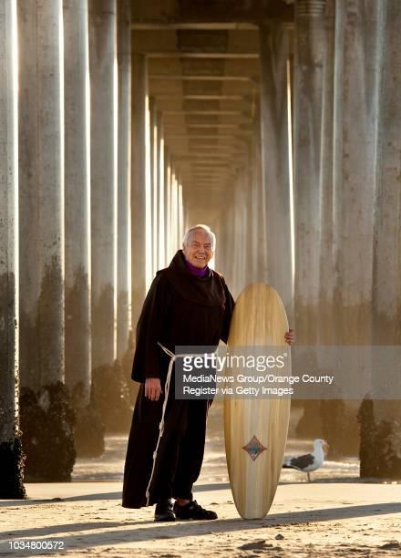Fr Christian Mondor a Franciscan brother at Sts Simon Jude Parish in Huntington Beach with his surfboard beneath the Huntington Beach pier We should...