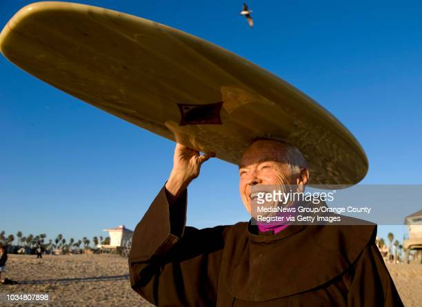 Fr. Christian Mondor a Franciscan brother at Sts. Simon & Jude Parish in Huntington Beach carries his surfboard near the Huntington Beach pier. Fr....