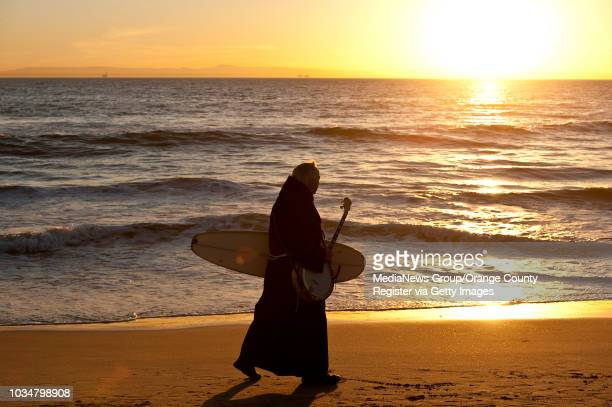 Fr. Christian Mondor walks along the surf with his banjo and surfboard for a photo in Huntington Beach. ///ADDITIONAL INFORMATION: read_surfpriest Ð...