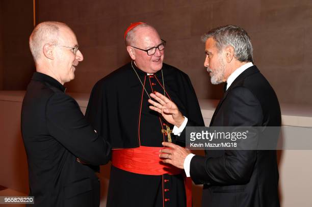 Fr James Martin Timothy Cardinal Dolan George Clooney attends the Heavenly Bodies Fashion The Catholic Imagination Costume Institute Gala at The...