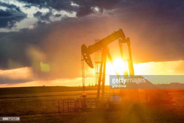 Fracking Pump Jack at Dusk with Sunset