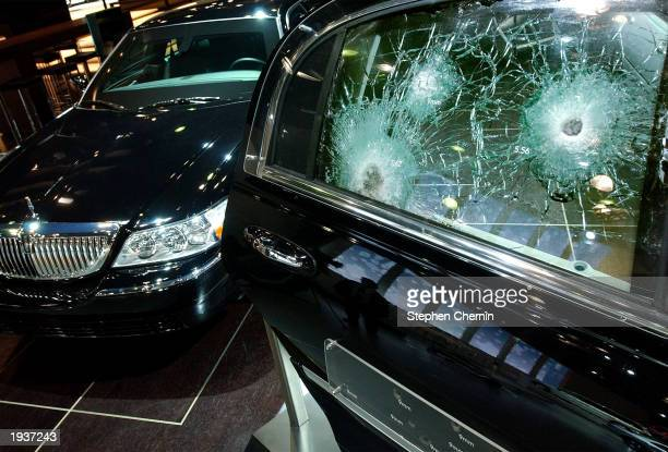 Fractured ballistic glass on a door is shown adjacent to the 2004 Lincoln Town Car Ballistic Protection Series car at the New York International Auto...