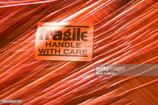 'fragile handle with care' sticker and plastic wrap on shipping box - fragile sticker stock pictures, royalty-free photos & images