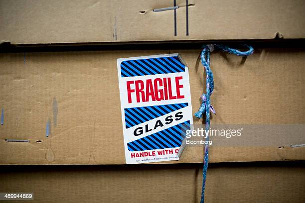 A 'fragile' sticker is displayed on a box of glass at Nam Wah Neonlight Electrical Mfy Ltd in Hong Kong China on Monday April 28 2014 Handpainted...