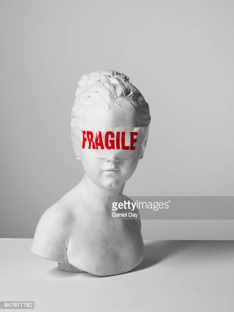 Fragile tape wrapped around the eyes of a plaster bust with object on her head
