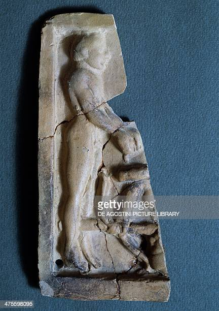 Fragment of a terracotta relief depicting Heracles carrying the two Cercopes brothers tied to a pole from the Sanctuary of the Chthonic Deities in...