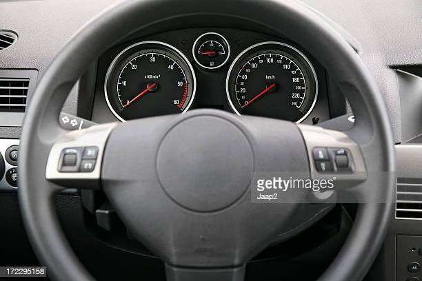 Fragment of car dashboard with steering wheel and meters