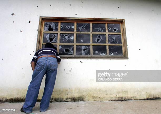 Un periodista observa el 28 de setiembre de 2006 los destrozos causados dentro de la vivienda del convicto colombiano Jorge Batres quien murio el...