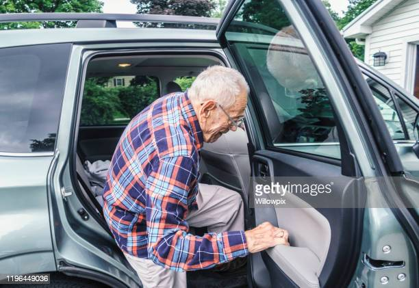 frail elderly man struggling to exit from car - disembarking stock pictures, royalty-free photos & images