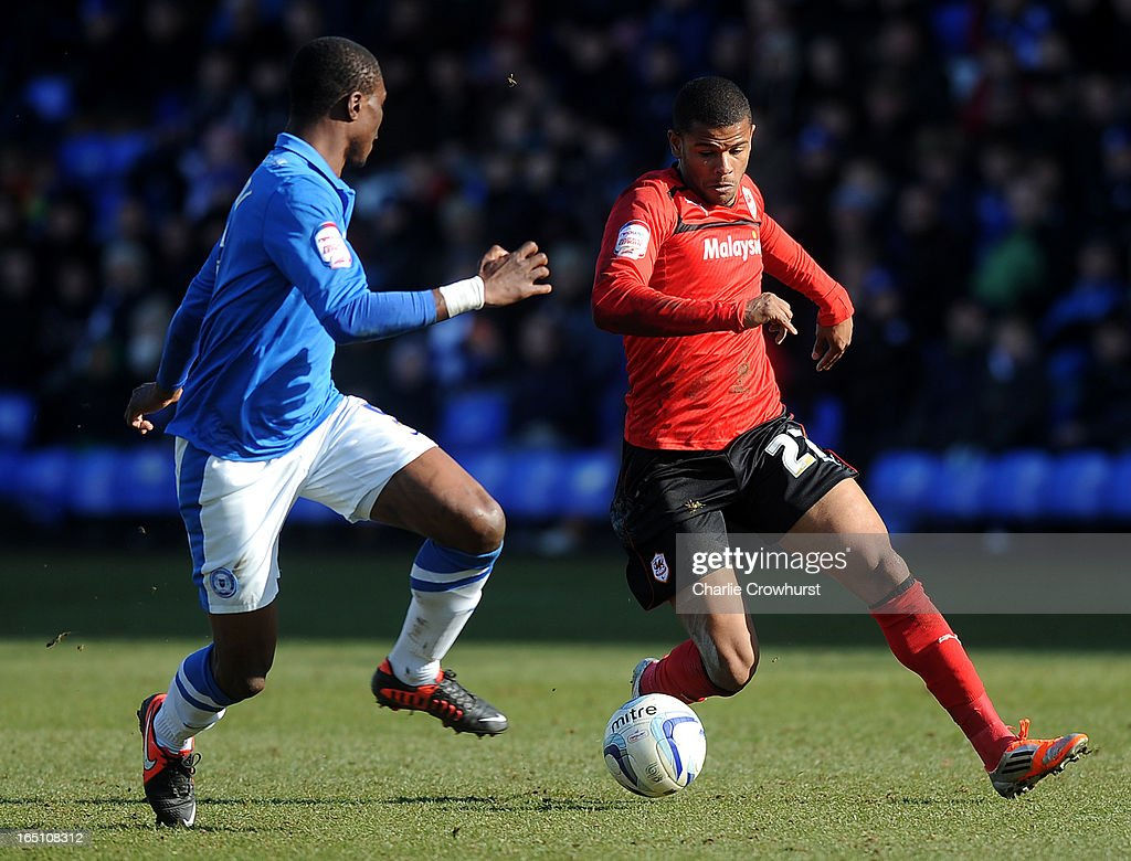 Fraizer Campbell of Cardiff City attacks Peterborough defender Gabriel Zakuani during the npower Championship match between Peterborough United and Cardiff City at London Road on March 30, 2013 in Peterborough, England,