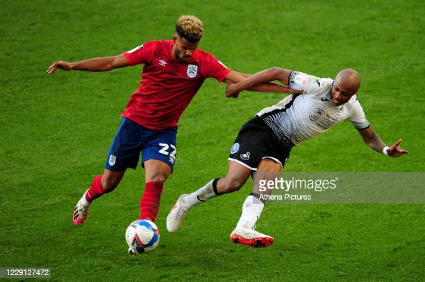Fraizer Campbell of Huddersfield Town battles with André Ayew of Swansea City during the Sky Bet Championship match between Swansea City and...