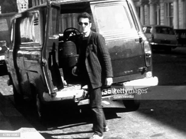 A frame from a Super8 film of musician Joe Strummer of English pub rock group The 101ers loading a van outside his squat in Orsett Terrace London W2...