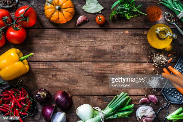 Frame of assorted fresh vegetables on rustic wooden table