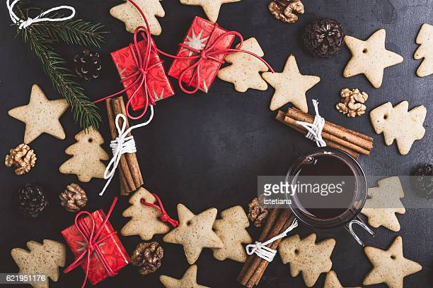 Frame of gingerbread cookies, spices and hot chocolate on blue table with copy space
