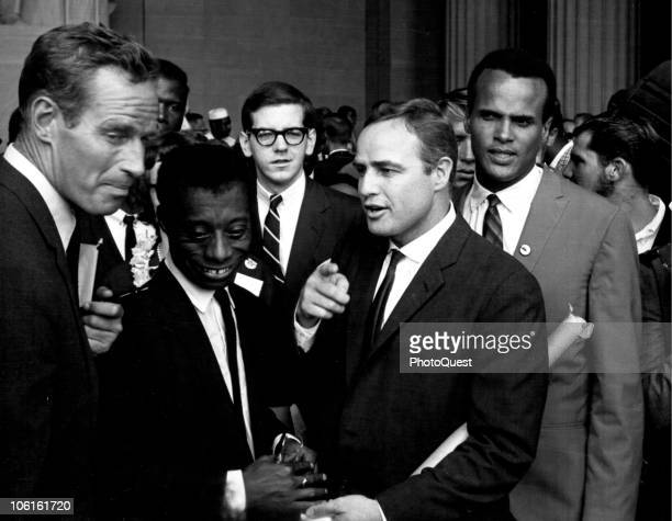 Framed by American actor Charleton Heston and singer Harry Belafonte writer James Baldwin talks with actor Marlon Brando in the Lincoln Memorial...