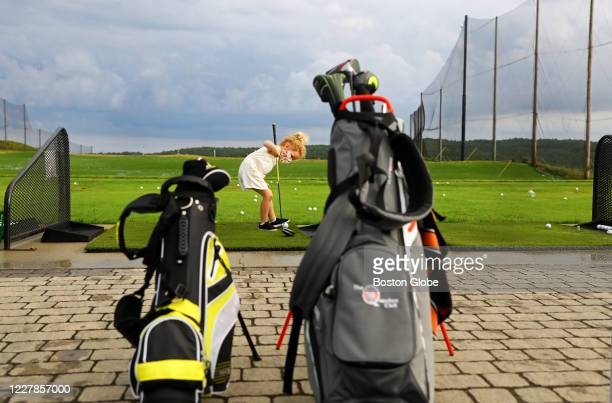 Framed by her junior clubs and those of her dad, a young girl works on the driving range at the Granite Links Golf Club in Quincy, MA on July 23,...