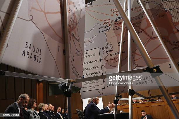 Framed by maps titled 'ISIL Ambition' US Defense Secretary Chuck Hagel testifies before the Senate Armed Services Committee in the Hart Senate Office...