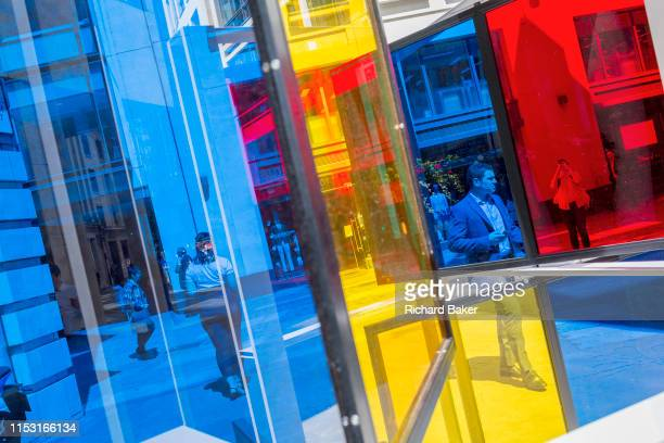 Framed by multicolored glass panels City workers walk along Lime Street during the lunchtime break in the City of London the capital's financial...
