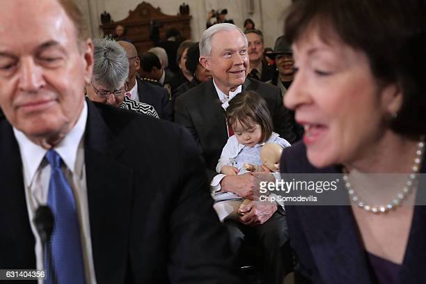 Framed by Sen Richard Shelby and Sen Susan Collins Sen Jeff Sessions holds one of his granddaughters before the start of his confirmation hearing to...