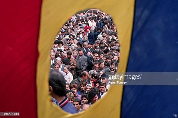 Framed by the hole in a Romanian flag where the Communist symbol used to be residents of Bucharest wait in line to vote in the 1990 elections