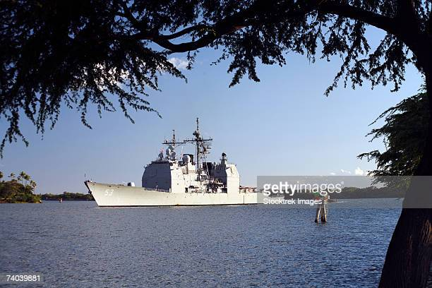 framed by trees on ford island the uss mobile bay, cg-53, transits into pearl harbor channel, with a tow craft standing by, following extensive operations in the hawaiian operating area during the multi-national exercise rimpac-06. - meerkanal stock-fotos und bilder