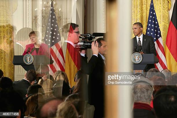 Framed in the language translation booth windows German Chancellor Angela Merkel and US President Barack Obama hold a joint news conference in the...