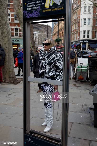 Framed in the missing panels of a map of the capital's West End theatre district, a woman fashionista wearing a monochrome outfit stands outside in...