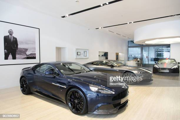 A framed photograph of actor Daniel Craig in his role as James Bond 007 hangs above Aston Martin automobiles left Vanquish centre DB11 and Rapide S...