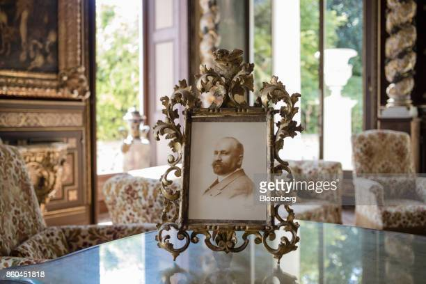 A framed photograph of Louis Alexandre Marnier Lapostolle sits on a table top in a sitting inside the Villa Les Cedres a 187yearold000squarefoot...