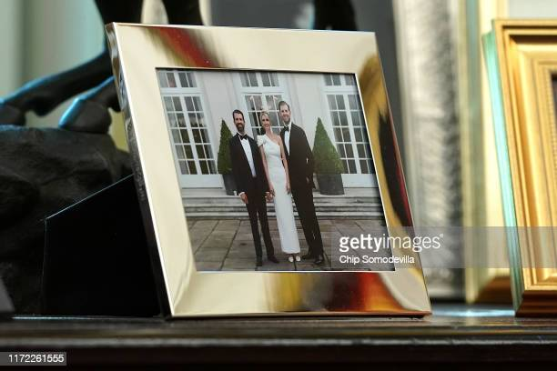A framed photograph of US President Donald Trump's children Donald Trump Jr Ivanka Trump and Eric Trump sits on a table behind the president's desk...