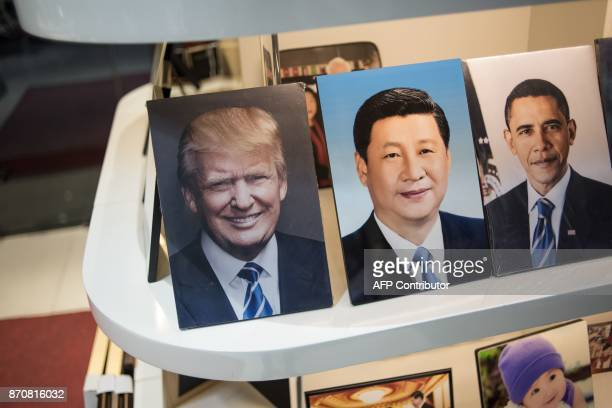 Framed photographs of Chinese President Xi Jinping US President Donald Trump and former US president Barack Obama are displayed in a photo shop in...