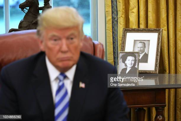 Framed photographs of U.S. President Donald Trump's parents, Fred and Mary Trump, sit on a table in the Oval Office while the president meets with...