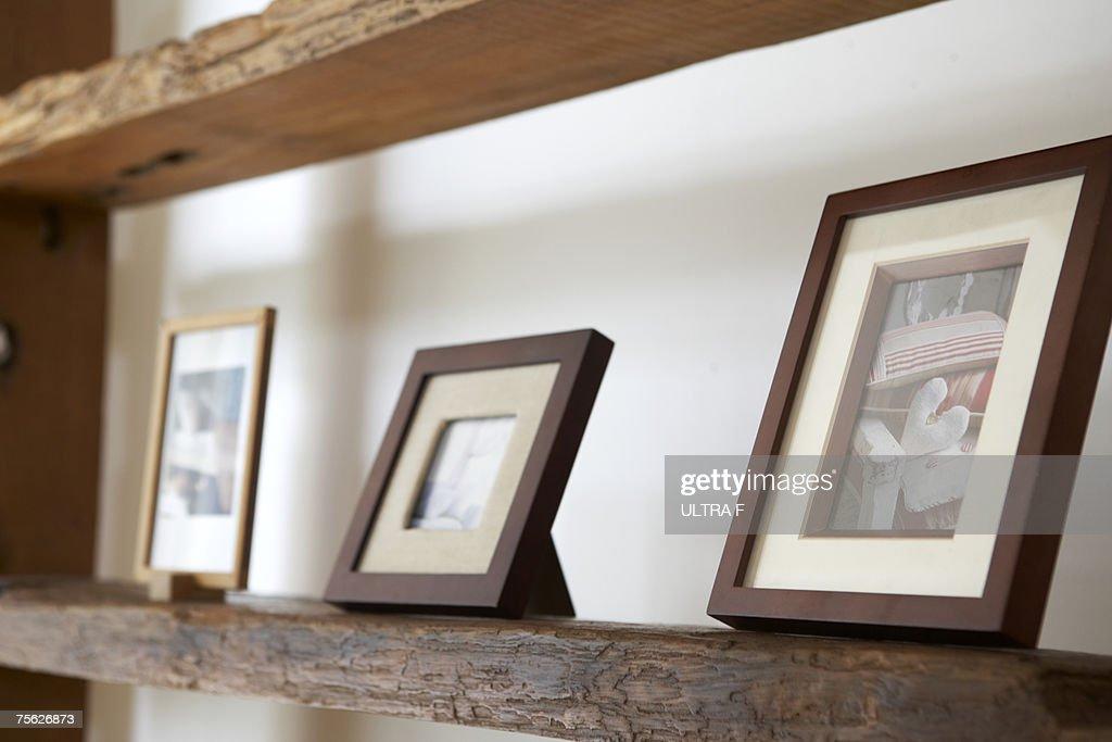 Framed photos on wooden shelf, close-up : Stock Photo