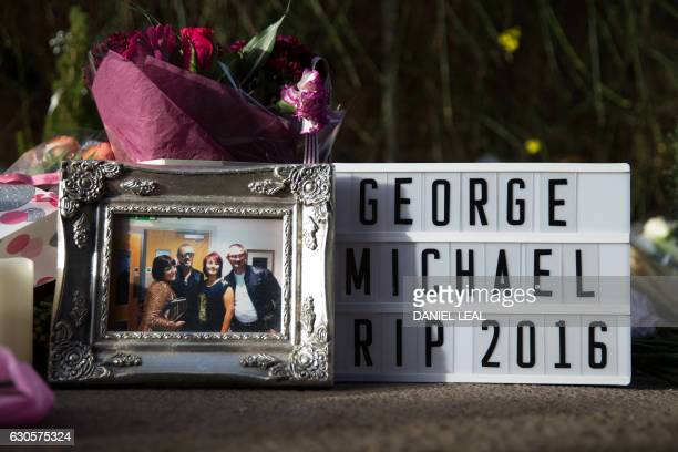 A framed picture is seen placed with other tributes outside the home of British singer George Michael where the singer died on Christmas Day in the...