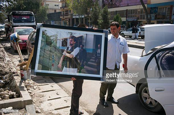 A framed picture of former mujahideen leader Ahmad Shah Massoud is carried to a car August 30 2015 in Kabul Afghanistan A political and military...