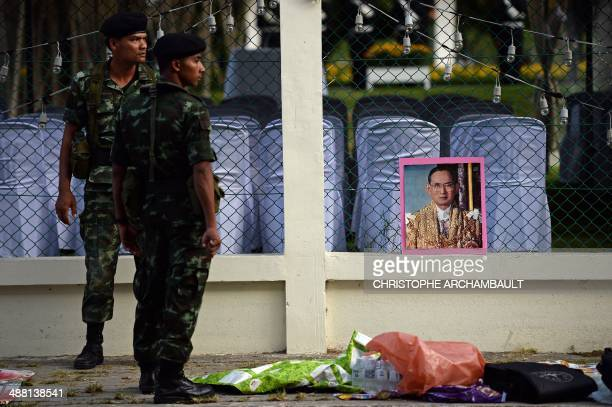 A framed picture of Thai King Bhumibol Adulyadej sits on the wall surrounding the Royal Palace as Thai soldiers patrol on the eve of the King's...