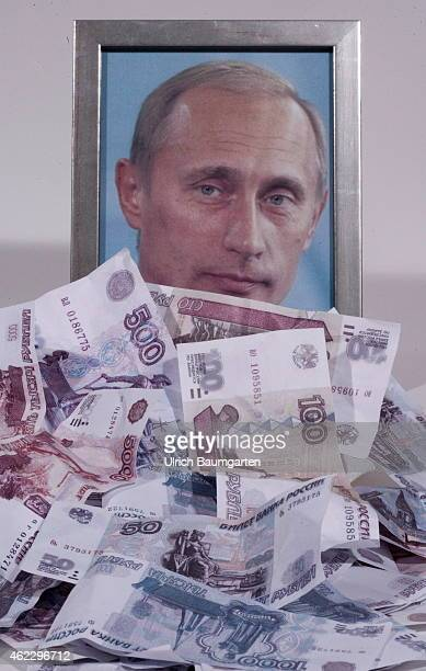 Framed Putin photo behind a pile of crumpled ruble banknotes Symbol photo on the topics of rubles decay economy activity in Russia etc on January 26...